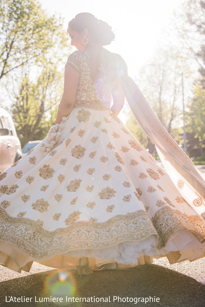 Dreamy Indian bride's capture  posing outdoors with wedding dress.