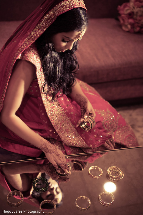 Lovely Indian bride getting her bangles arranged to get them on.