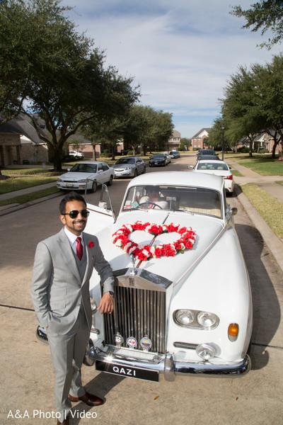Elegant indian groom posing with wedding car