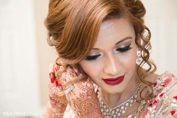 Sweet indian bride putting earrings on
