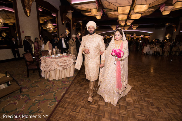Indian bride and groom walking in to the wedding reception capture.