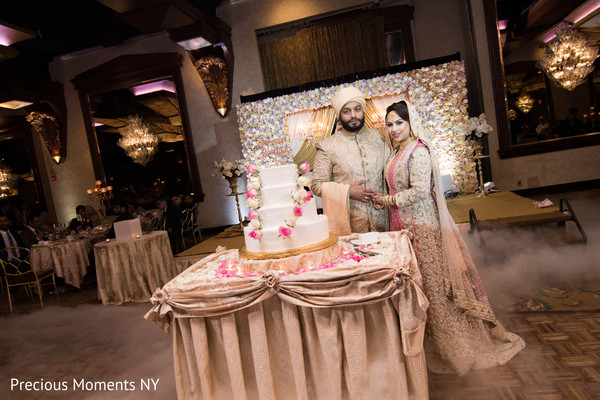 Lovely Indian bride and groom posing next to wedding cake photo.