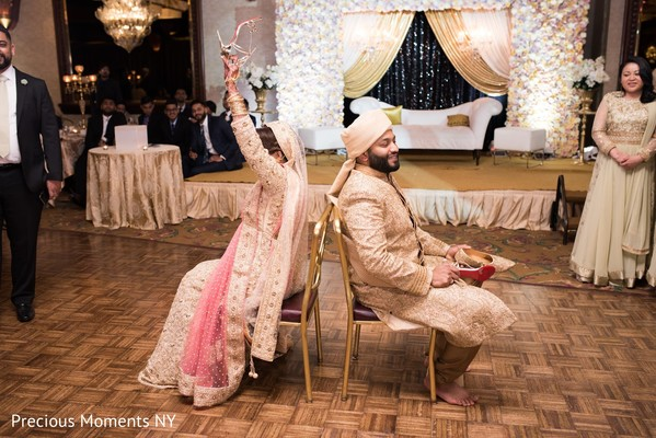 Indian bride and groom playing the shoe game capture.