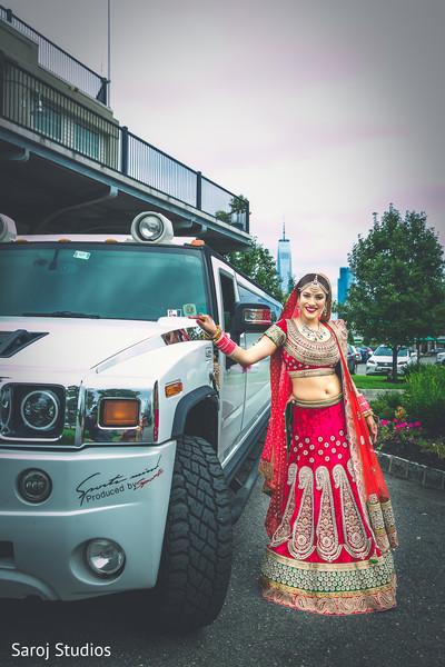 Indian bride posing next to limousine vehicle.