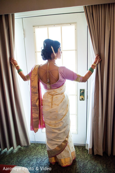 Adorable Indian bride looking out the window.