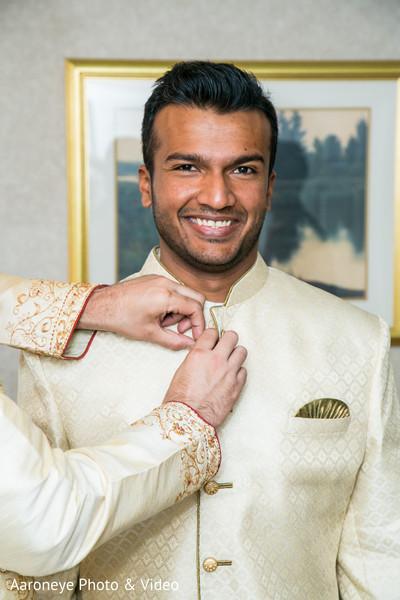 Indian groom being helped to get his sherwani.