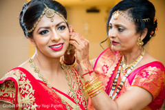 Beautiful indian bride's being helped with jewelry