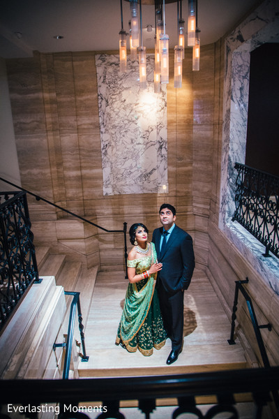 Stunning portrait of Indian bride and groom at the stairs to their wedding reception.