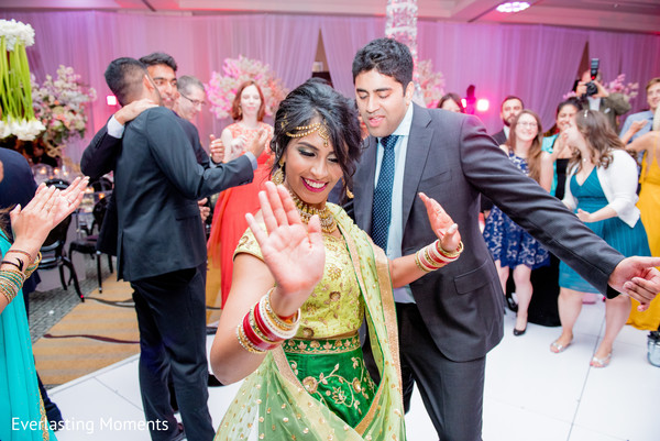 Joyful Indian bride and groom dance capture at wedding reception.