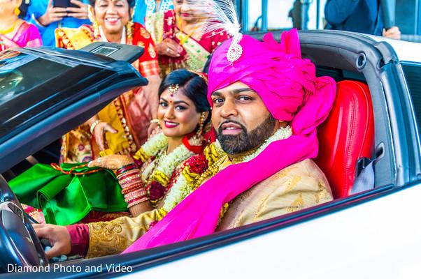 Indian bride and groom inside wedding car