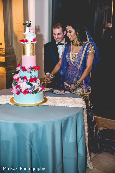Lovely capture Indian bride and groom cutting cake together.