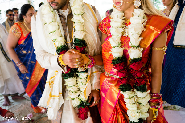 Indian bride and groom holding hands close up.