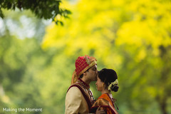 Adorable Indian bride being kissed by groom outdoor capture.