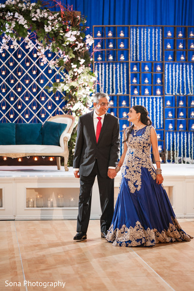 Indian bride walking in to wedding reception dance floor with father.