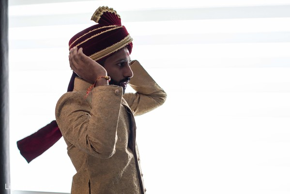 Indian groom getting his turban on portrait.