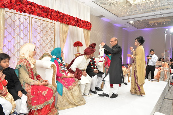 Indian groom getting a garland from parent.