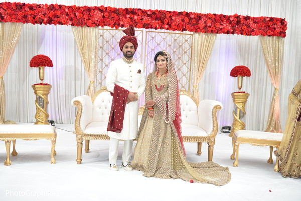Indian bride and groom posing at fascinating Indian wedding mandap flowers decoration.