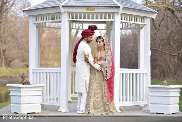 Joyful Indian  bride and groom holding capture.