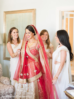 Indian bride getting her Ghoonghat put by bridesmaids.