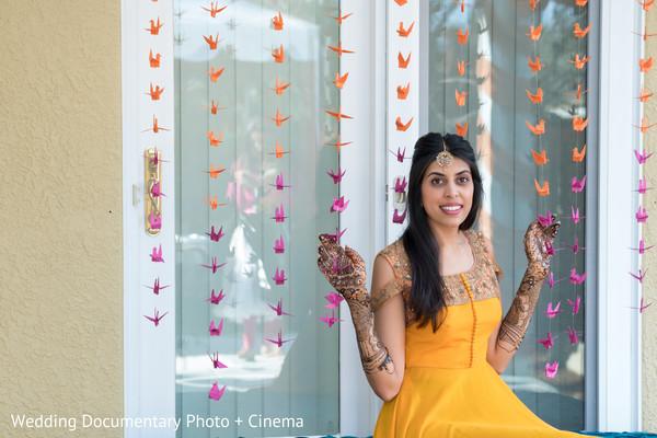 Gorgeous Indian bride posing with her mehndi art.