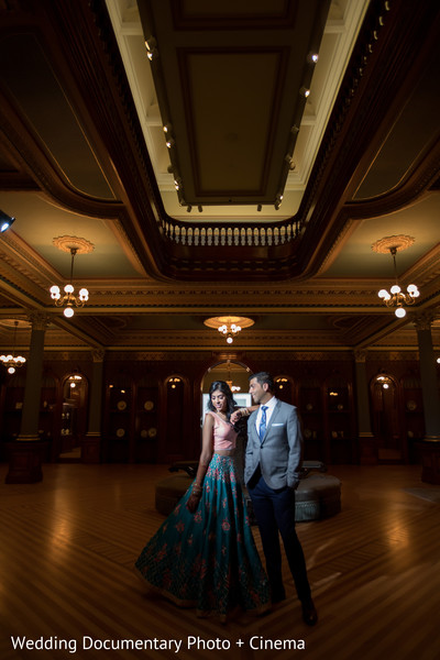 Indian bride and groom posing indoors for photo shoot.