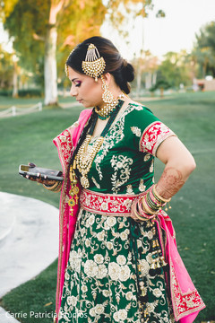 Gorgeous Indian bride in a golden and green sangeet outfit.