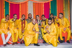 Indian bride and groom with groomsmen during sangeet celebration.