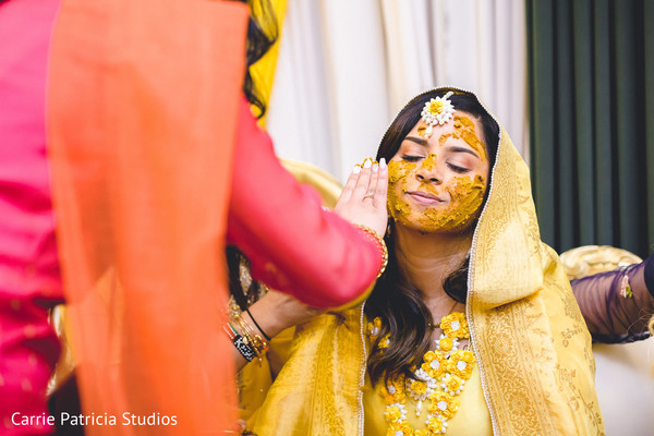 Lovely Indian bride getting turmeric paste on her face.