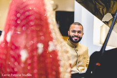 Glamorous Indian groom looking at bride.