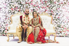 Stunning Indian Indian bride and groom at wedding reception mandap flower decorations.