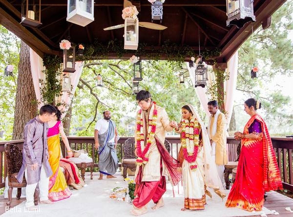 Enchanting Indian bride walking behind groom at wedding ritual.