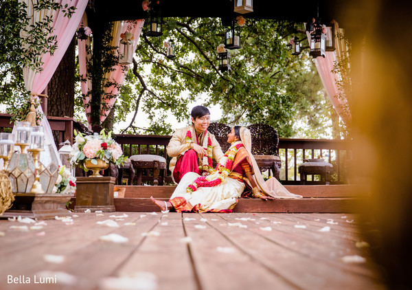 Dreamy Indian bride and groom on their ceremony outfit in an outdoors portrait.