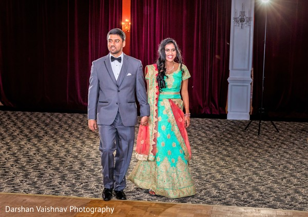 Ravishing Indian bride and groom making their entrance to wedding reception.