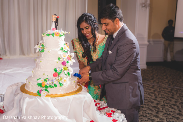 Gorgeous Indian bride and groom cutting cake moment.