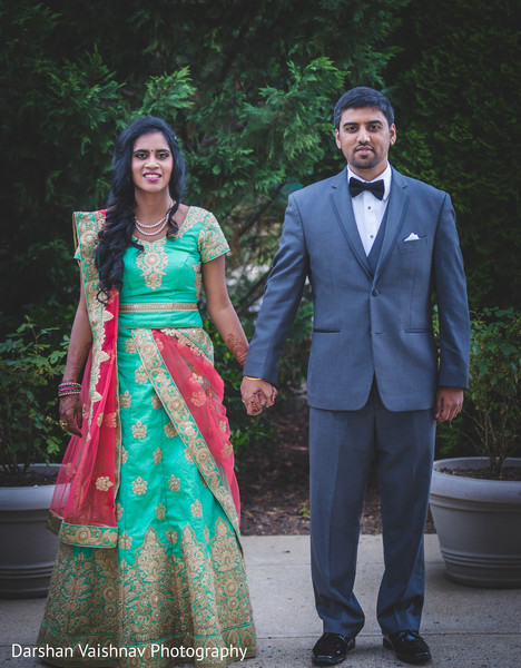 Joyful Indian  bride and groom holding hands looking at camera photo.