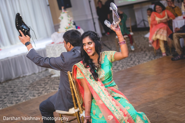 Indian bride and groom playing the shoe game.