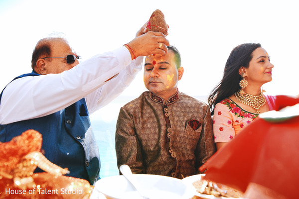Indian groom is smeared in yellow turmeric paste at his first wedding ceremony ritual