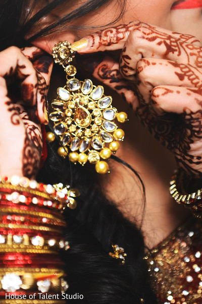 Indian bride putting earring on