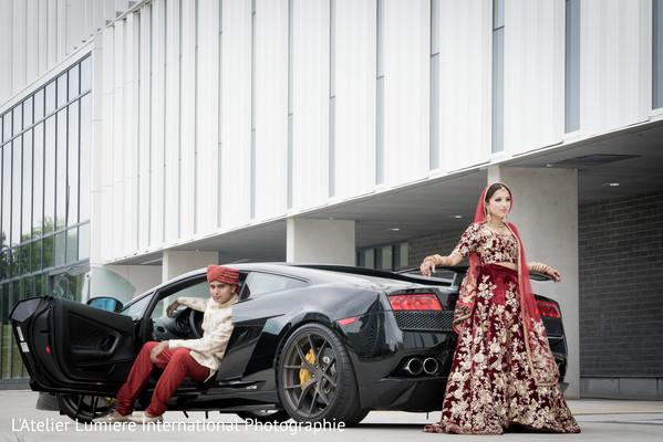Indian lovebirds posing next to wedding car