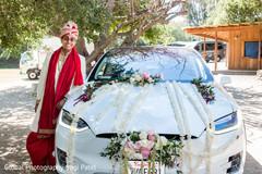 Indian groom posing next to wedding car