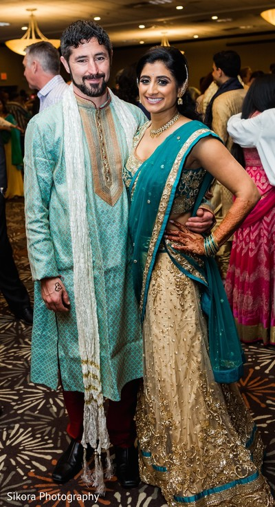 Indian couple posing at wedding reception.