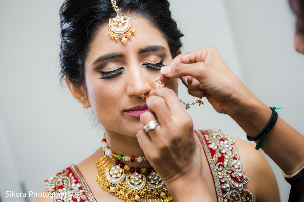 Indian bride putting her nose earring.