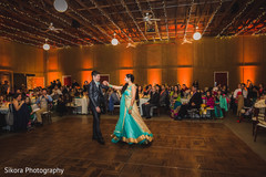 Joyful Indian bride and groom dancing.