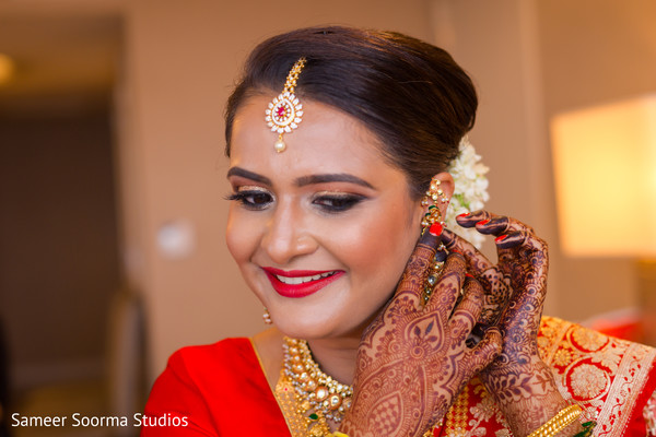 Gorgeous indian bride putting earrings on