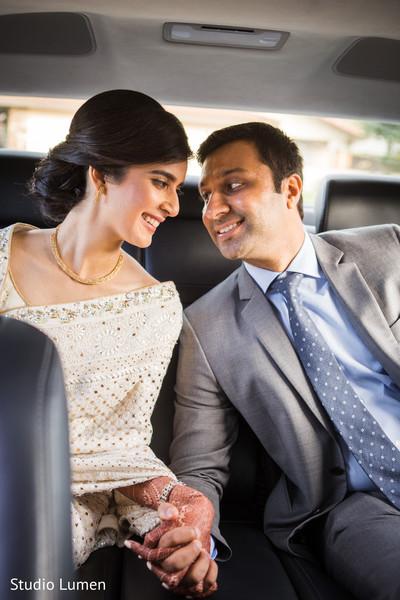 Lovely indian couple inside wedding car