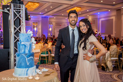Lovely indian couple posing next to wedding cake