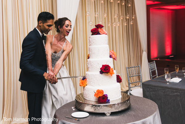 Indian couple cutting their wedding cake with a sword