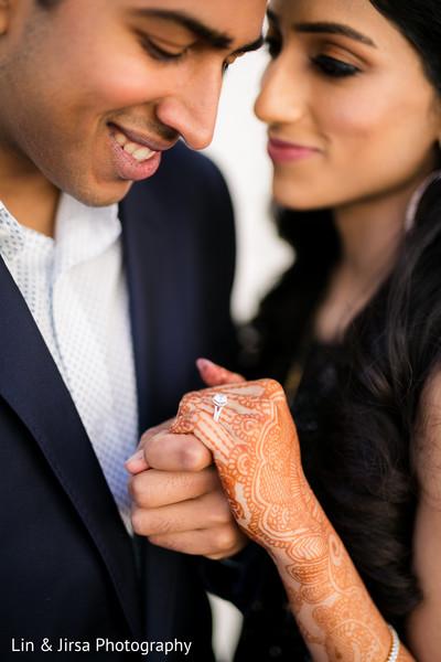 Indian groom admiring bride's engagement ring