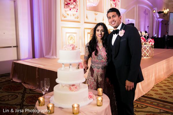 Lovely indian couple posing with wedding cake