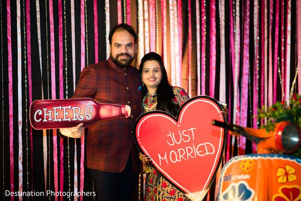 Indian wedding guests posing with photo booth props | Photo